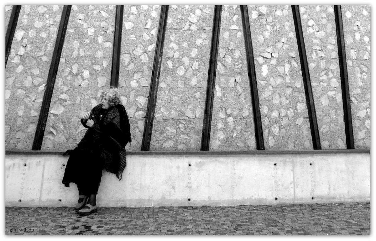 "Helen Aron at the Holocaust Museum, Johannesburg, 2019 (photographer Gail Wilson). This photo captures Helen's mood and sadness in response to the visit to the Museum. Lewis Levin was the architect. Here the exterior façade is clad with ""railway lines"" and stones embedded in the concrete. Railway lines, transportation to death camps and cattle trucks represented the journeys of so many Holocaust Victims. The railway line images are not straight but are intended to show confusion of genocide. Helen's parents in the thirties fled to South Africa to give birth to the next generation."